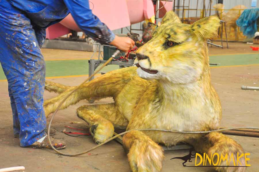 The worker is painting on animatronic Cougar